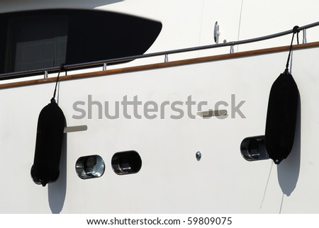 Super yacht moored in harbor at Cannes. Cote d'Azur. France. Showing side of hull with fenders and portholes. - stock photo