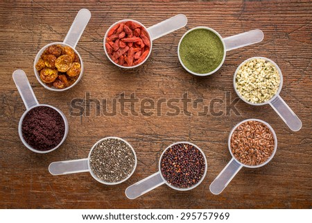 superfood abstract (wheatgrass, acai berry, goji berry, flax seed,chia seed,goldenberry,hemp seed, quinoa grain) - top view of measuring scoops surrounding  a copy space on a rustic wood - stock photo