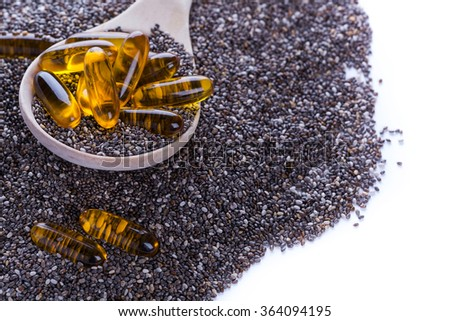 Superfood for vegans - chia seeds powerful of vegetal Omega-3 oil. Soft gel pills in wooden spoon on dry chia seeds background, selective focus - stock photo