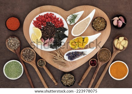 Superfood immune boosting selection in white porcelain dishes and wooden bowls over heart shaped board and lokta paper background. - stock photo