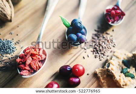 Superfood: Spoons of various healthy superfoods on wooden background