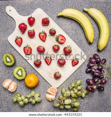 Superfoods and healthy lifestyle or detox diet food concept bananas, strawberries, light and dark grapes, kiwi and tangerine on a granite table top view - stock photo