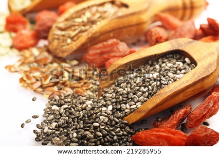 Superfoods in wooden scoops (seeds of chia, hemp and flax and Goji berries) - stock photo