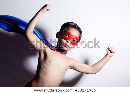 Superhero!  Adorable, mixed race boy wearing a mask and cape and showing off his muscles.   - stock photo