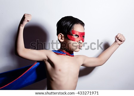 Superhero!  Adorable, mixed race boy wearing a mask and cape and showing off his muscles.