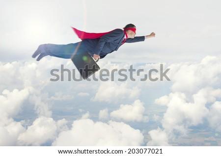 superhero businessman flying above the clouds - stock photo