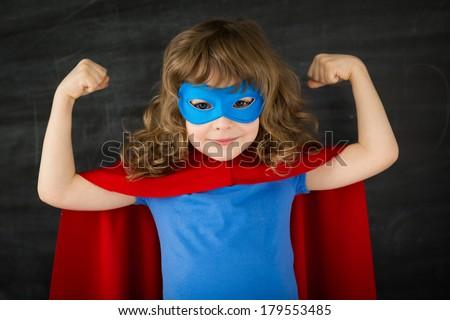Superhero kid against school blackboard - stock photo