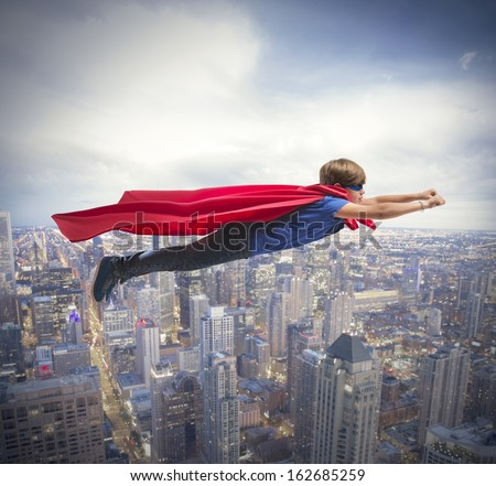 Superhero kid flying fast over the city - stock photo