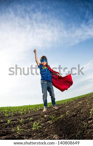 Superhero kid jumping against dramatic blue sky background - stock photo