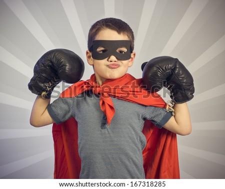 Superhero kid wearing boxing gloves - stock photo