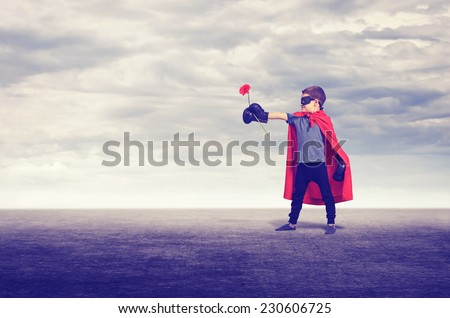 Superhero kid wearing boxing gloves and flower outdoors. - stock photo