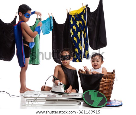 Superhero Laundry Day.  Three adorable brothers dressed as superheroes and ironing and hanging their clothes on the line.  Isolated on white.   - stock photo