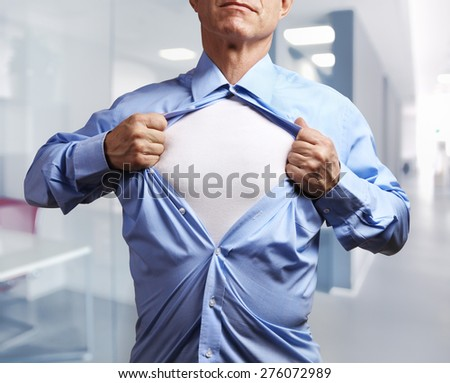 Superhero. Mature businessman tearing his shirt off over office background - stock photo