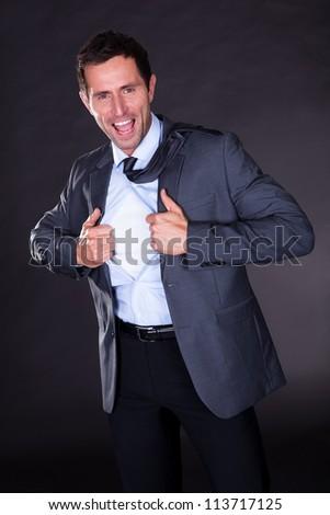 Superhero Tearing Off His Shirt On Black Background - stock photo