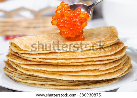Superimposition of red caviar on pancakes