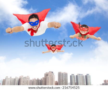 superman and daughters  flying in the sky with buildings background  - stock photo