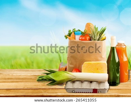 Supermarket. Brown table and on background blured supermarket and bag with products - stock photo