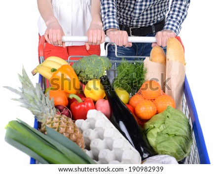 Supermarket. Happy couple with a shopping cart. Isolated over white background. - stock photo