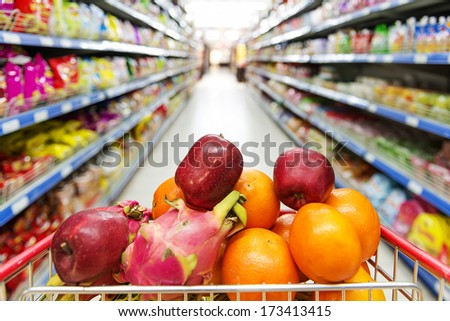 Supermarket interior, filled with the fruit of the shopping cart. - stock photo
