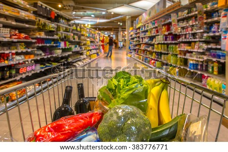 Supermarket trolley at an  aisle filled up with healthy vegetables seen from the consumers point of view from above - stock photo