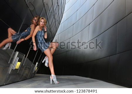 Supermodel posing sexy in front of modern metallic wall background - stock photo
