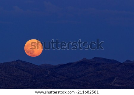 Supermoon rising over desert mountains in Barstow, California. - stock photo