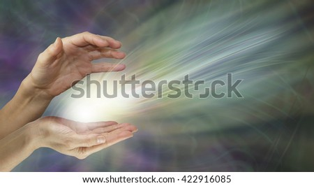 Supernatural electromagnetic energy field - female healer's hands with a radiating white light energy formation between on a wide muted green and purple background with copy space - stock photo