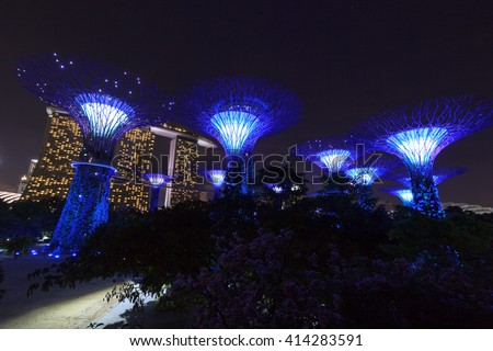 Supertree grove and Marina Bay Sands at night in Gardens by the Bay, Singapore - stock photo
