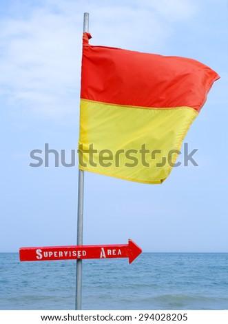 Supervised Area Arrow Sign and Flag on a Beach - stock photo