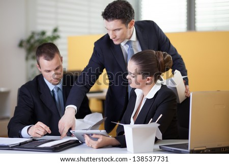 Supervisor checking on office workers work during lunch break - stock photo