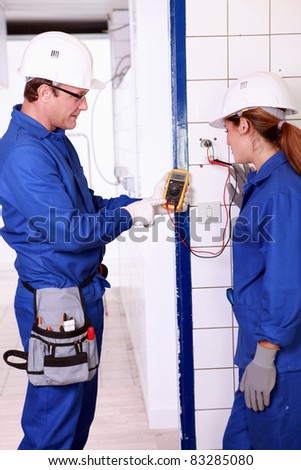 Supervisor explaining work to female electrician apprentice - stock photo