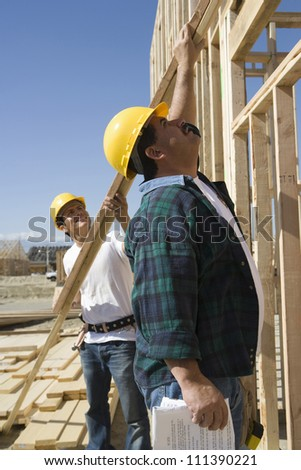 Supervisor helping coworker at construction site - stock photo