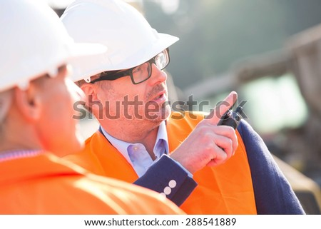 Supervisor showing something to colleague at construction site - stock photo