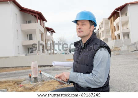 Supervisor using electronic tab on construction site - stock photo