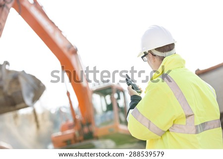 Supervisor using walkie-talkie at construction site against clear sky - stock photo