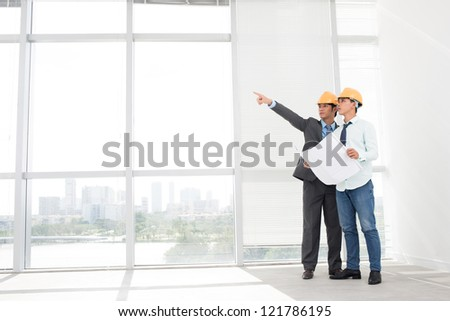 Supervisors in hardhats inspecting empty office premises - stock photo