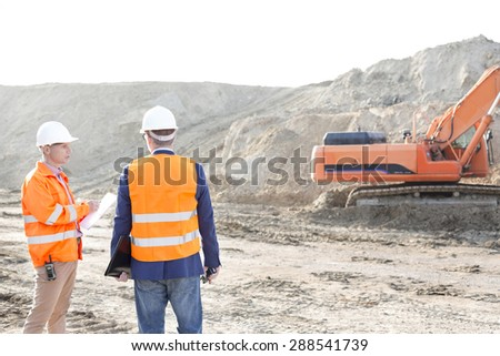 Supervisors standing at construction site against clear sky - stock photo