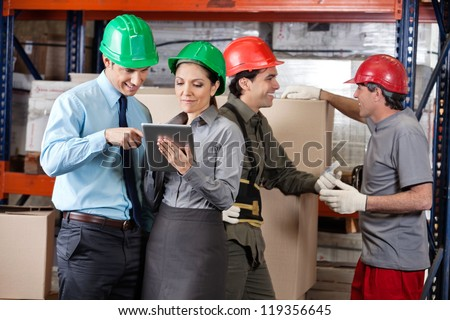 Supervisors using digital tablet and foremen discussing work at warehouse - stock photo