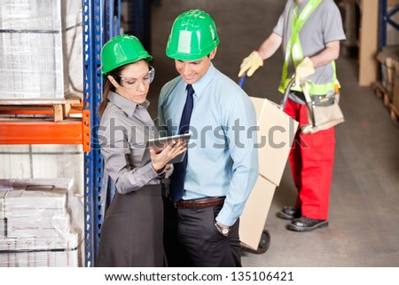 Supervisors using digital tablet with foreman working at warehouse - stock photo