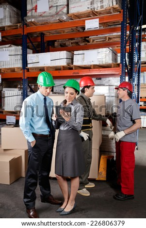 Supervisors using digital tablet with foremen discussing work at warehouse - stock photo