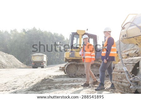 Supervisors walking at construction site against clear sky - stock photo