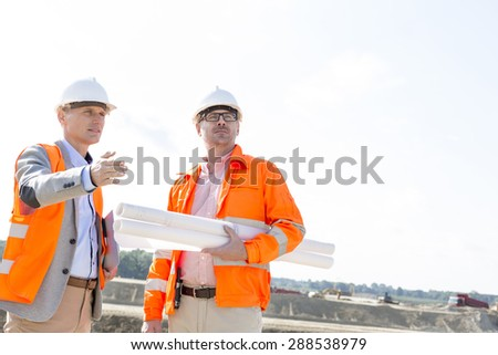 Supervisors with blueprints discussing at construction site against clear sky - stock photo