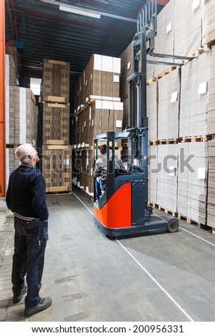 Supervizor oversees a pallettruck reaching high up while grabbing a pallet from the top shelf - stock photo