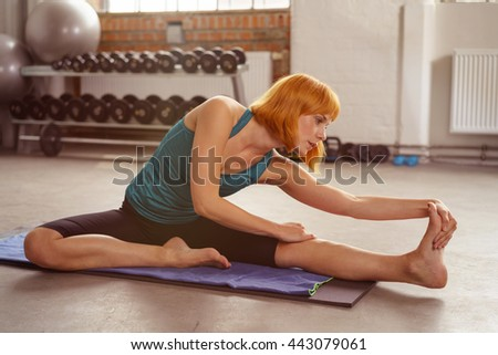 Supple young woman doing stretching exercises on a yoga mat at a gym to warm up her muscles before a workout - stock photo