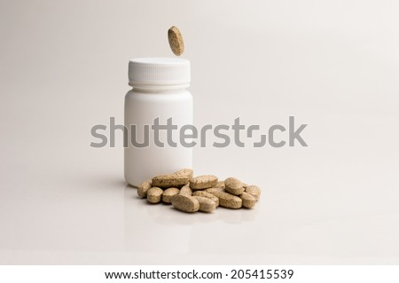 Supplements on gray background with supplements bottle - stock photo