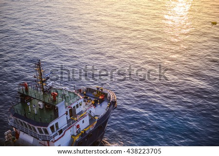 Supply boat caught buoy beside the jack up oil rig for supply food and equipment - stock photo