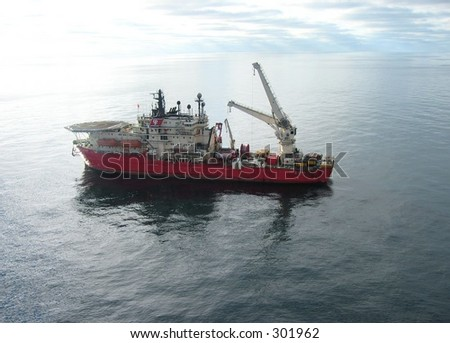 Supply boat steering an ROV (remotely operated vehicle), fishing for lost equipment. - stock photo