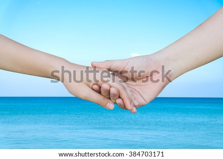 support and assistance human hands on blurred blue ocean background,helping hand concept.close up soul mate handshake touching together:love affection:instagram color filter effect:better life concept - stock photo