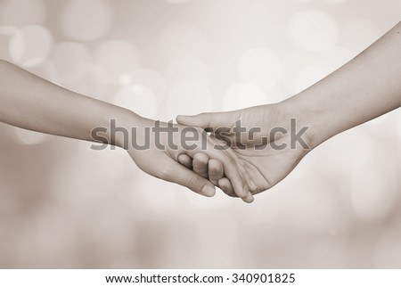 support assistance human hands on blurred bokeh tan background,helping hand concept.close up lovers soul mate handshake touch together:love affection:picture in vintage sepia tone color filter effect - stock photo