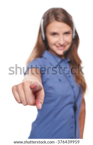 Support phone operator in headset smiling looking at camera and pointing at you, isolated on white. Shallow depth of field, focus on finger - stock photo